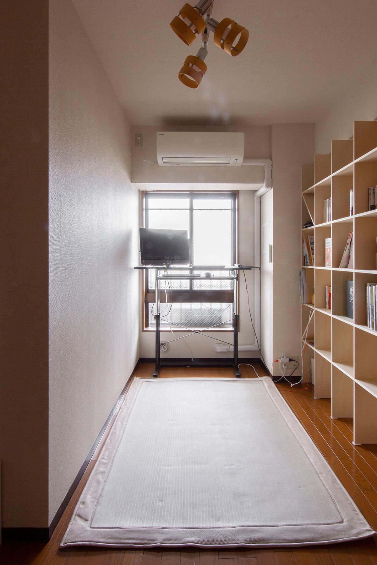 壁一面の本棚とスタンディングデスクのある書斎