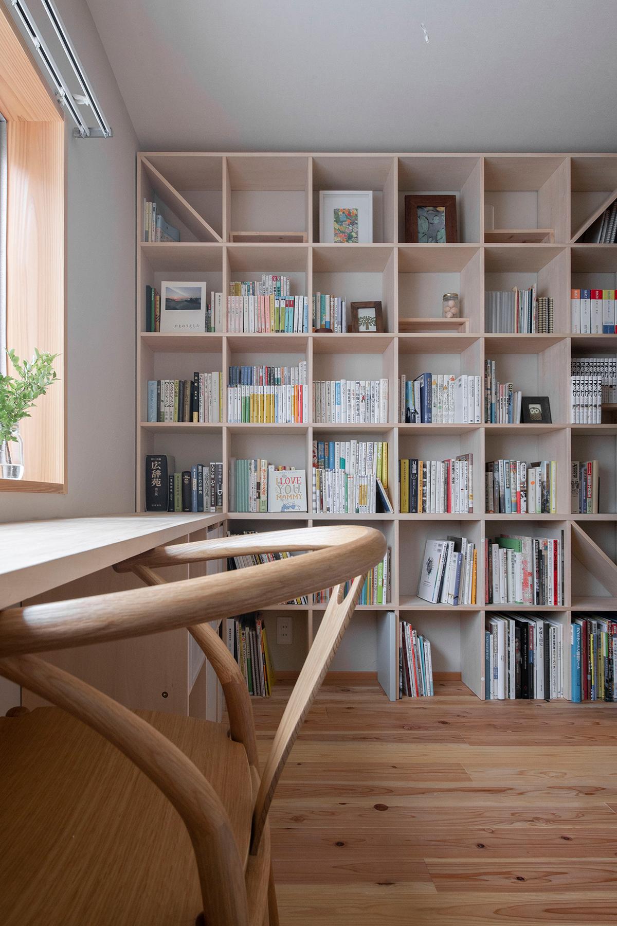 ワークデスクと壁一面の本棚をL型に構成