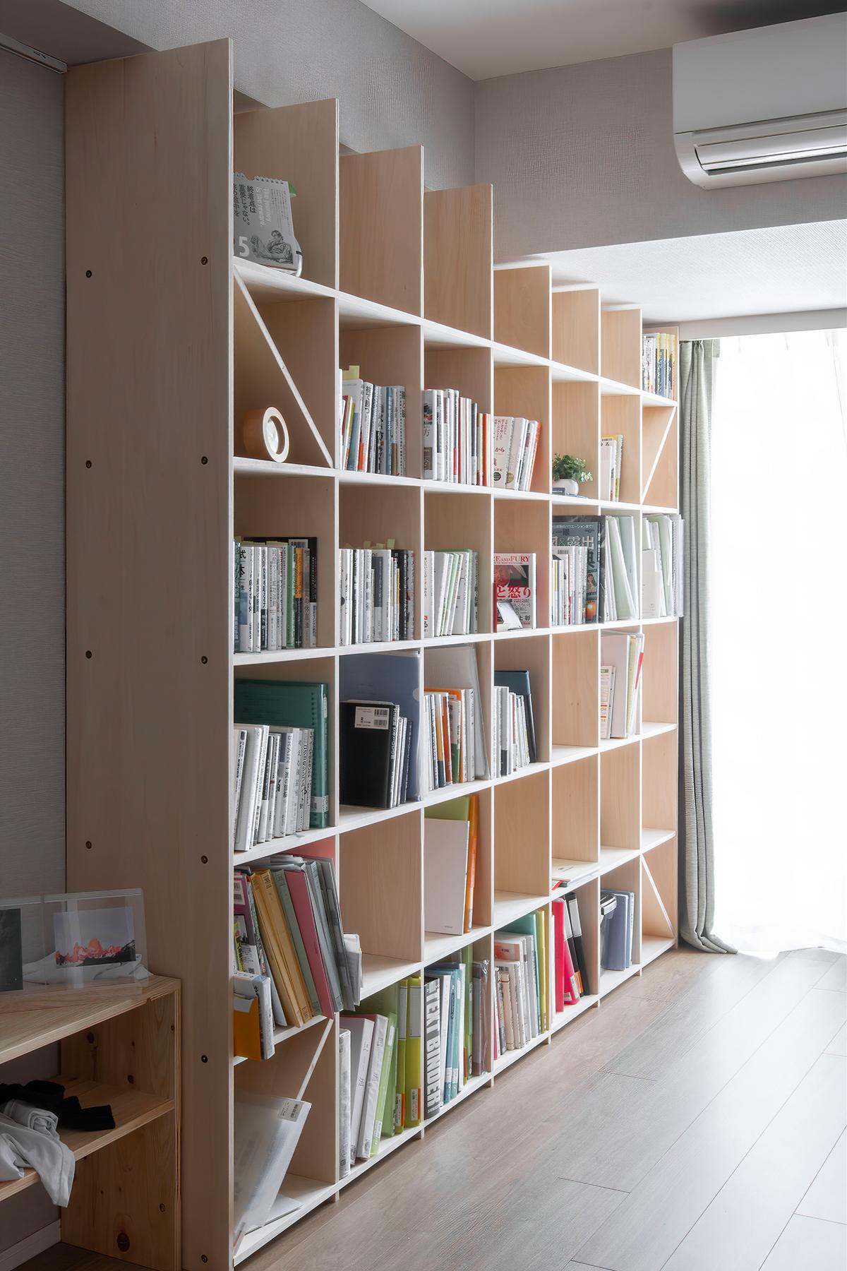 壁一面の本棚と並ぶスタンディングデスク
