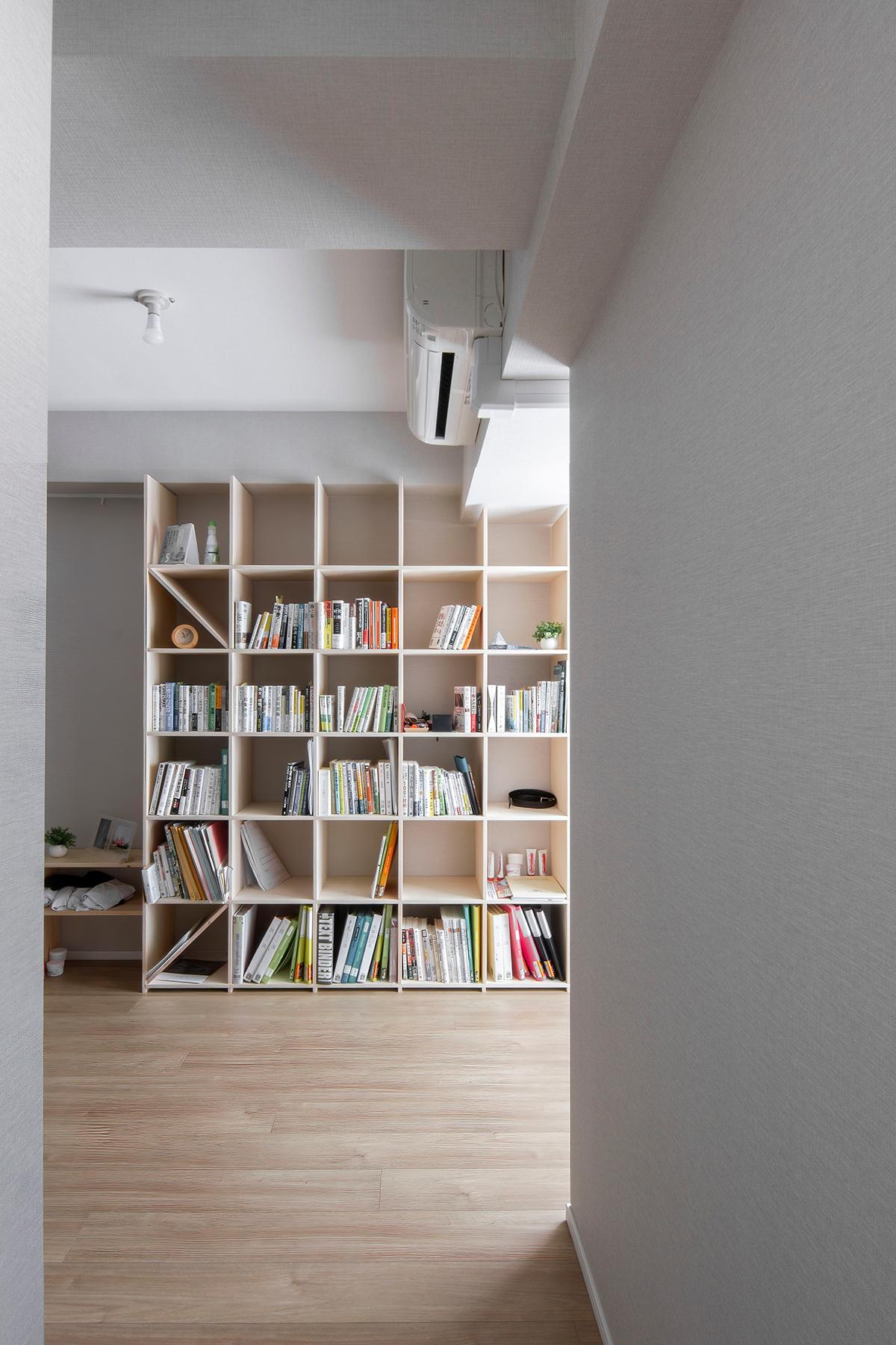 壁一面の本棚と並行にスタンディングデスク