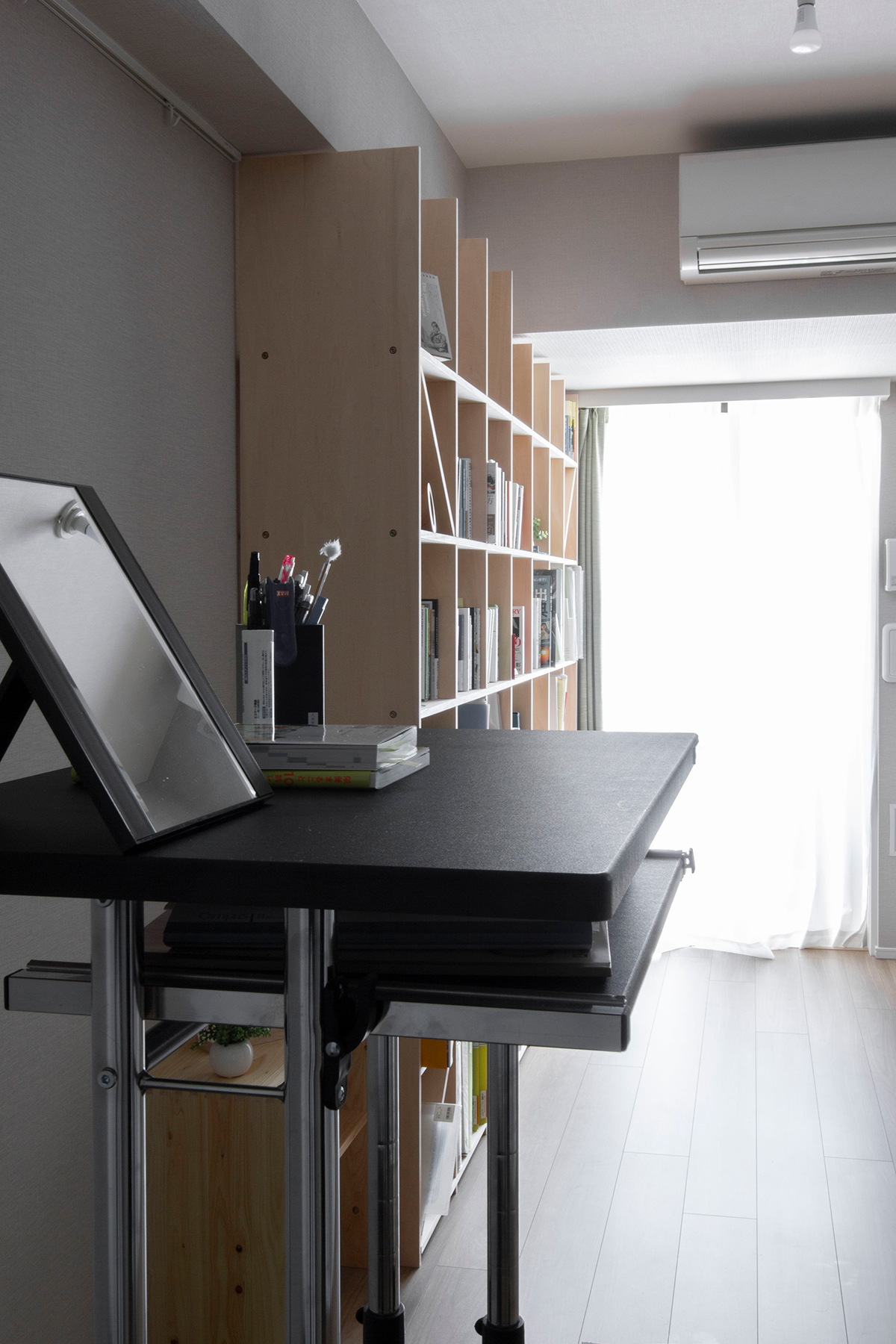 壁一面の本棚とスタンディングデスク