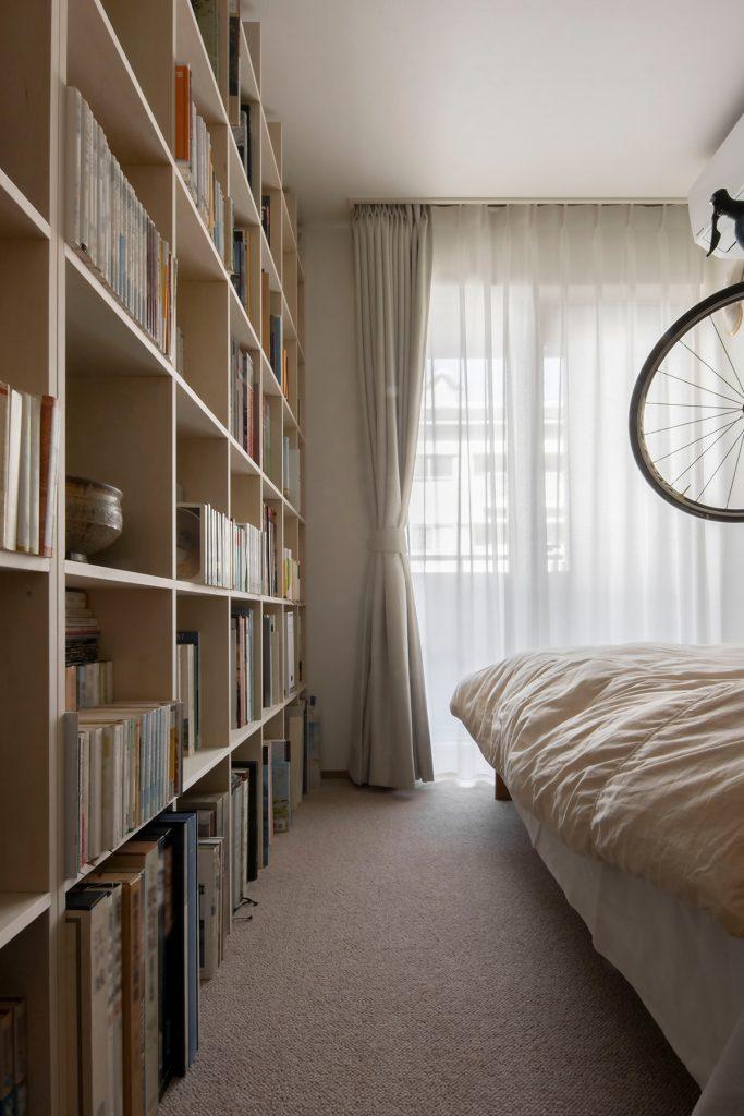 """""""自転車を飾る壁一面の本棚"""