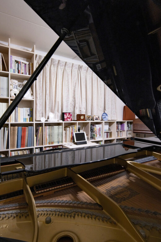 ピアノ2台が並ぶ音楽室の壁面に | 壁一面の本棚 奥行350mm ロータイプ / Shelf (No.14) | マルゲリータ使用例